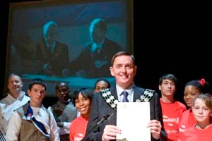 Mayor of Newham and children on stage with projection screen in background