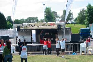 outside stage in park with dj and people watching