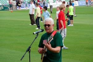 man singing into microphone with guitar on cricket outfield