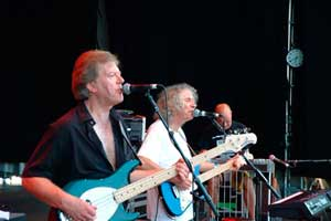 two men on stage singing and playing electric guitar